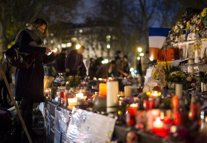 Varias personas recuerdan a las víctimas de los atentados terroristas en el Monumento a la República en París. (Archivo/EFE)