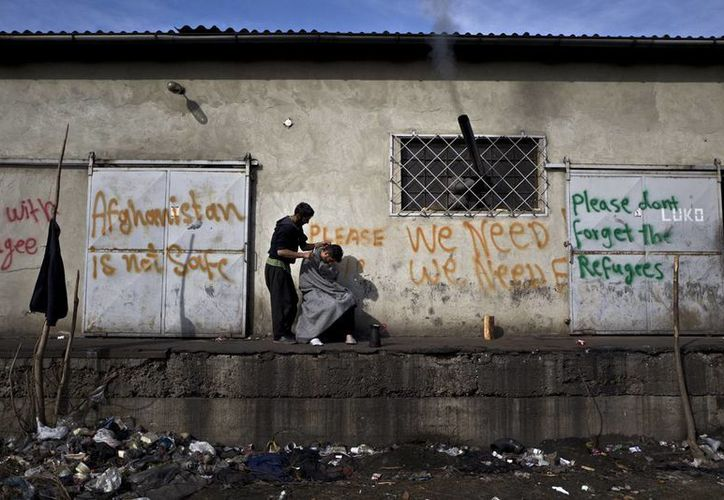 Alemania recibió 890 mil solicitudes de asilo en 2015 y desde entonces ha buscado agilizar su estancia o regresándolos a su país. Imagen de contexto de un refugiado afgano mientras le corta el cabello a un amigo, en un almacén abandonado donde viven. (AP Photo / Muhammed Muheisen)