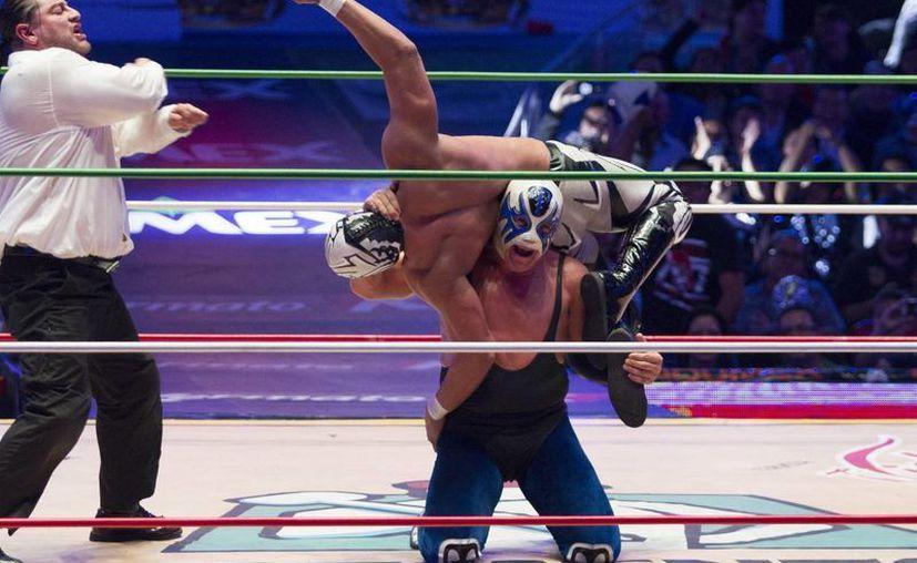 La lucha estelar del festejo de aniversario del CMLL, el pasado viernes, entre Atlantis y La Sombra. Este lunes el consejo cumple 82 años de hacer vibrar a los aficionados al arte del pancracio. (Archivo Notimex)