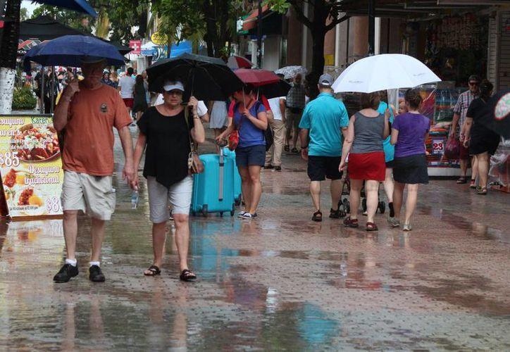 A pesa de las lluvias que bañaron a Playa del Carmen este miércoles, hubo visitantes que recorrieron el centro turístico. (Daniel Pacheco/SIPSE)