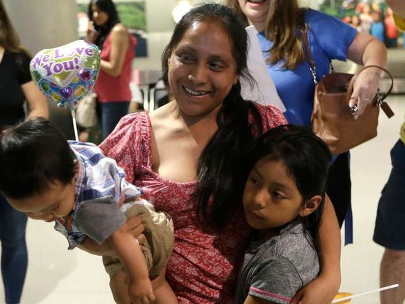 Buena Ventura Godínez, center,  holds her son Pedro, left, as she is reunited with her daughter Janne, Right, at Miami International Airport.