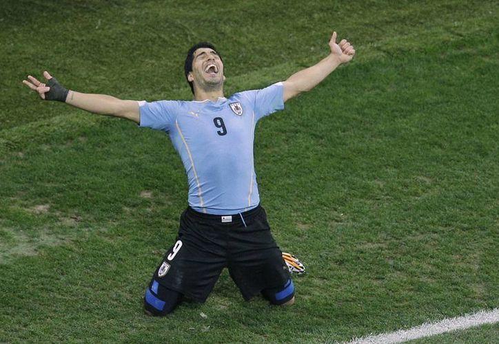 Luis Suárez celebra su segundo gol ante Inglaterra en el Mundial de Brasil. Ahora Suárez formará una tripleta de ensueño en el Barza junto con Neymar y Messi. (Foto: AP)