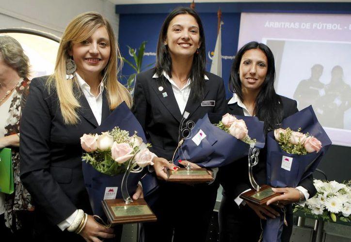 Las árbitras Mariana Corbo (i) Claudia Umpiérrez (c) y Luciana Mascaraña (d) en el reconocimientos que les brindaron en Montevideo, Uruguay. (EFE)