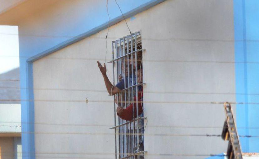 Imagen de presos gritando desde una ventana del penal de Topo Chico, lugar donde fallecieron 49 personas durante un enfrentamiento. (Agencias)