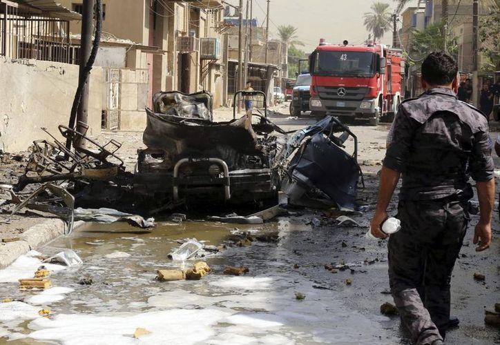 Un policía camina por el lugar donde se ha registrado un atentado con coche bomba cerca de la comisaría de policía de Al-saadon en Bagdad, Irak. (Archivo/EFE)
