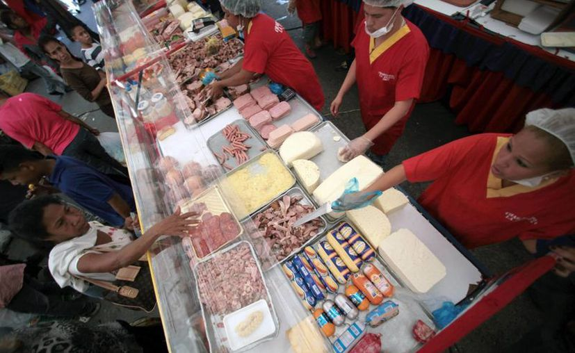 Gente comprando alimentos a precios subsidiados en un supermercado estatal de Caracas. (Agencias)