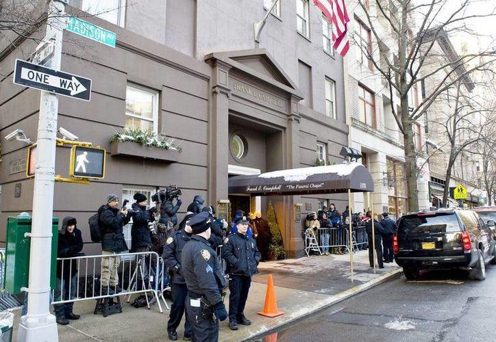 Periodistas y policías permanecen a las afueras del lugar donde se lleva a cabo el velorio del actor estadounidense Philip Seymour Hoffman, en la Funeraria Campbell de Nueva York, E.U. (EFE)