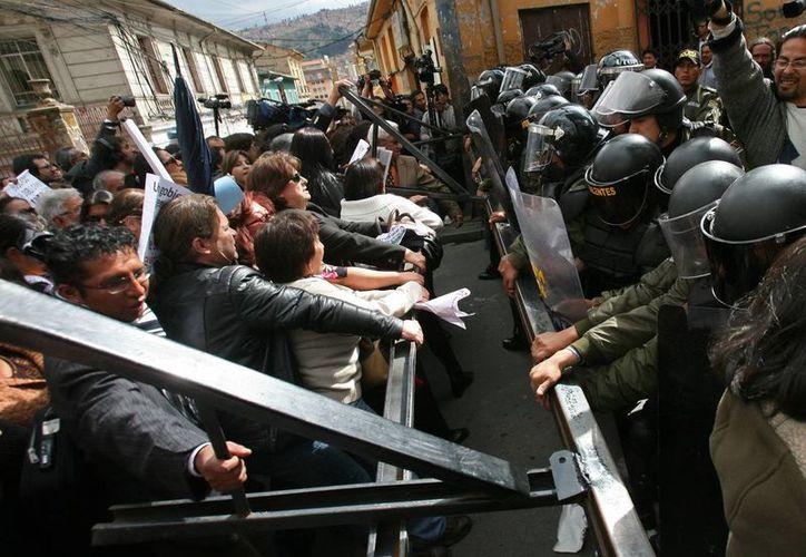 Trabajadores de medios de comunicación y activistas durante un enfrentamiento con la policía en el transcurso de una marcha en Bolivia para repudiar la violencia machista. (EFE)