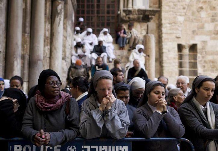 Monjas católicas rezan delante de la Iglesia del Santo Sepulcro en el casco viejo de Jerusalén. (EFE)