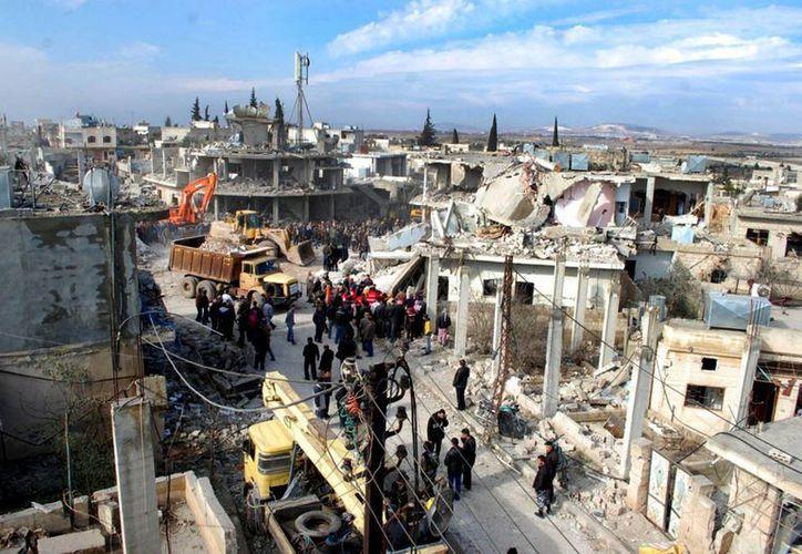 Varias personas se reúnen donde estalló un coche bomba cerca de una escuela en la aldaea de al-Kaffat, en la provincia de Hama, en el centro de Siria. (Agencias)