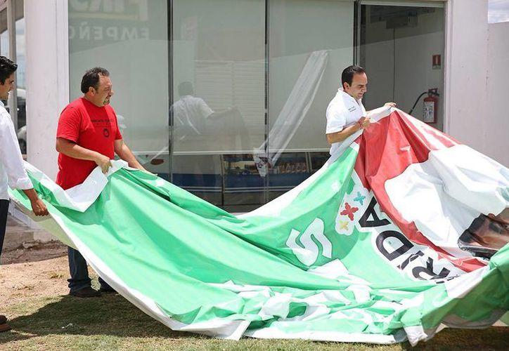 Daniel Granja Peniche, Francisco Torres Rivas y Nerio Torres Arcila retiran una lona en Mérida con propuestas del PRI. (SIPSE)