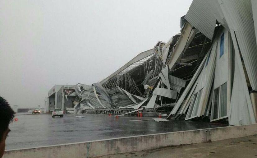 """Los fuertes vientos y las constantes lluvias ocasionaron daños al hangar de la empresa """"Pilatus PC-12 Center de México"""". (La Vanguardia)"""