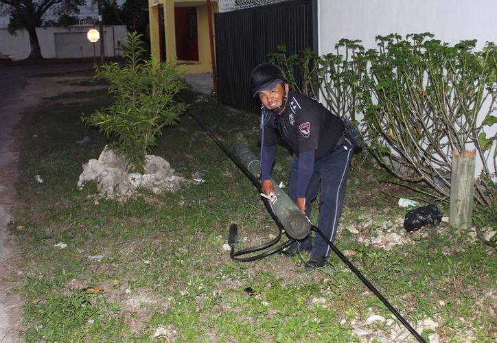 Un elemento de la policía que acudió al lugar retirando el poste caído. (Redacción/SIPSE)