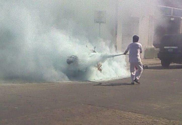 El comerciante chino Ching-Chuan Ling, conocido como 'Tony' en Progreso, sofoca el incendio en la moto estacionada. (Óscar Pérez/SIPSE)