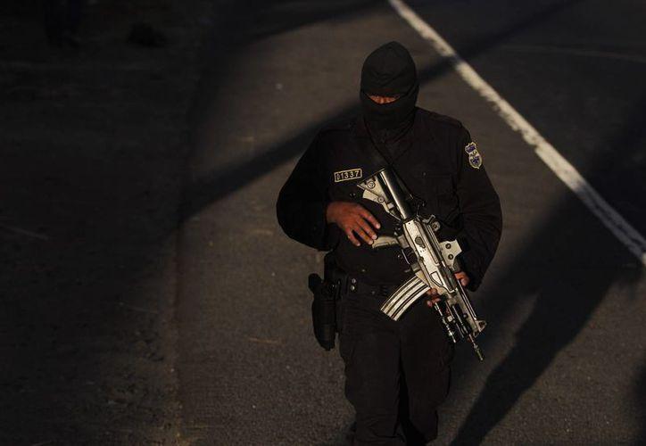 Un agente de la Policía Nacional Civil vigila las cercanías de la escena del crimen, en un estacionamiento de furgones, en Quezaltepeque, a unos 25 kilómetros al noroeste de San Salvador. (EFE)