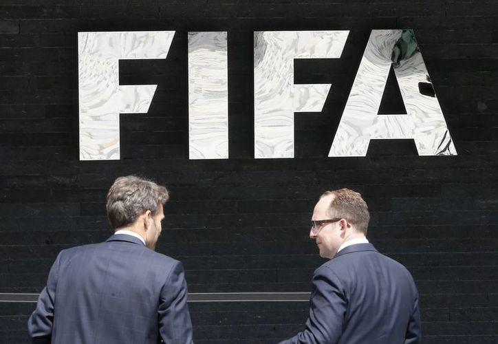 Dos hombres hablan entre sí de frente al logo de la FIFA en la sede de Zúrich , Suiza. Fiscales suizos abrieron procedimientos penales en la adjudicación de la FIFA de las Copas del Mundo de 2018 y 2022. (AP Photo/Michael Probst)