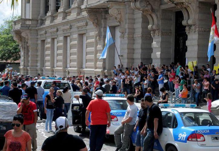Unos 300 miembros de la Policía de Santa Fe acompañados por sus esposas y familiares permanecían, este lunes 9 de diciembre de 2013, frente a la Casa de Gobierno provincial para reclamar un incremento salarial. (EFE)
