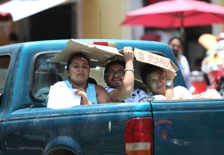 El Servicio Metereológico Nacional advirtió que este domingo se espera ambiente extremadamente caluroso en gran parte del país debido a una circulación de alta presión. Imagen de una familia protegiéndose del sol. (Notimex)