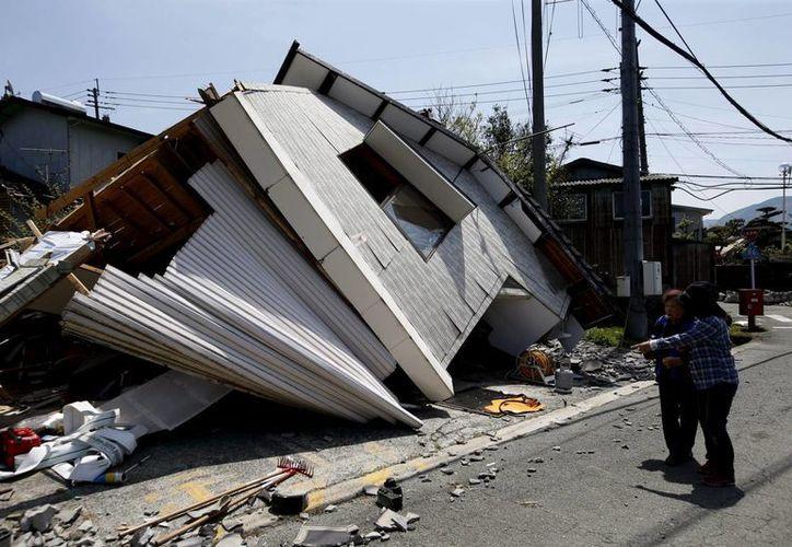 Dos mujeres observan el estado en el que ha quedado una casa tras un terremoto en Minamiaso, Japón. (EFE/Archivo)
