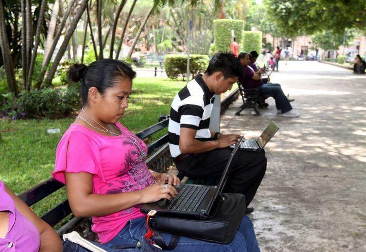 La Plaza Grande y el parque de San Juan, los sitios donde más gente se conecta al Internet. Imagen de contexto de dos personas sentadas en la Plaza Grande de Mérida, con su computadora. (Milenio Novedades)