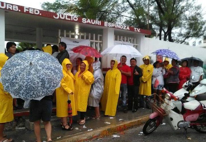 Los ciudadanos permanecieron formados con impermeables afuera de la primaria Julio Sauri Espinosa, de Isla Mujeres. (Redacción/SIPSE)