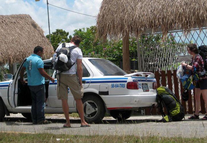 Taxistas de Bacalar denuncian que mientras ellos no pueden 'recoger' pasaje en Chetumal, sus colegas de la capital sí lo hacen en el Pueblo Mágico. (Javier Ortiz/SIPSE)