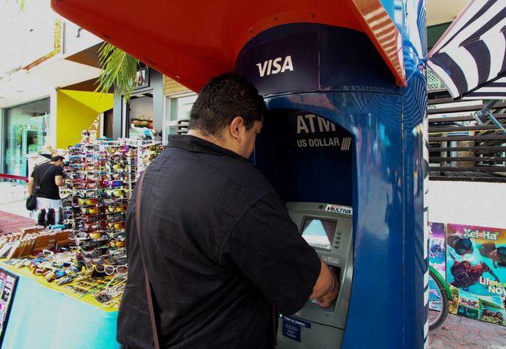 La Policía Federal brindará apoyo en ciberinteligencia para combatir delitos electrónicos que afectan a empresas financieras y a ciudadanos. Imagen de contexto de una personas realizando operaciones en un cajero automático.(Archivo/Notimex)