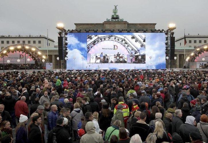 Visitantes reunidos enfrente de las Puertas de Brandenburgo en Berlín, para conmemorar 25 años de la caída del Muro de Berlín. (Fotos: AP)