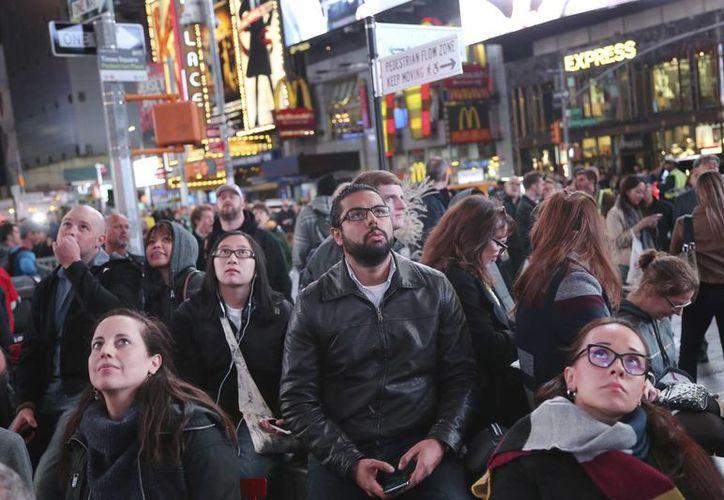 En el Times Square de Nueva York se reunen cientos de personas para mirar las pantallas donde se proyectan en directo los resultados de la histórica contienda electoral. (AP/Seth Wenig)