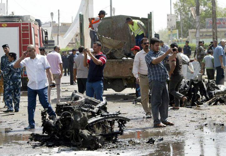 Iraquíes inspeccionan el lugar de un atentado con coche bomba en Basora, sur de Irak. (EFE)