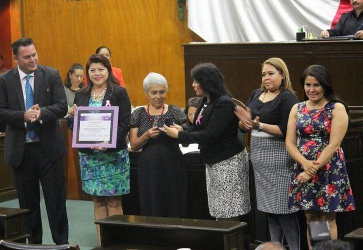 Momento en que Georgina Flores Vallejo recibe la presea Xochiquetzalli. (twitter/@UniondeMorelos)