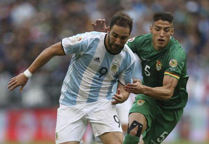 El defensa boliviano Nelson Cabrera (de verde)  no cumplió con los requisitos que exige la FIFA para que un jugador naturalizado juegue en una selección nacional, por lo que sancionó a Bolivia. La imagen es únicamente ilustrativa. (vivelhoy.com)