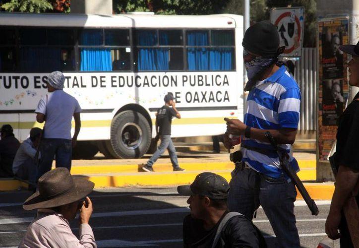 """En la fotografía,  habitantes del municipio de Santo Domingo Teojomulco, bloquen la carretera federal 190 frente al IEEPO, en enero de 2014. Según funcionarios, ocho de cada diez jefes del """"viejo"""" IEEPO pertenecían a la Sección 22 de la Coordinadora. (Archivo/ Notimex)"""