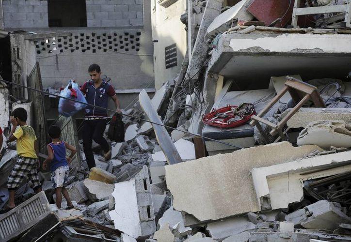 Muchachos palestinos rescatan algunas pertenencias de un edificio impactado por bombardeos israelíes en Ciudad Gaza. (Foto: AP/Adel Hana)