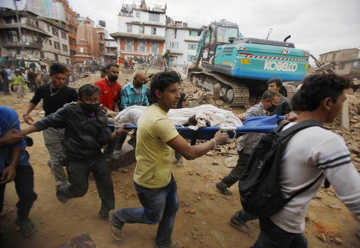 Voluntarios sacan los cuerpos de los escombros de los edificios que se vinieron abajo tras el sismo en Nepal. (Agencias)