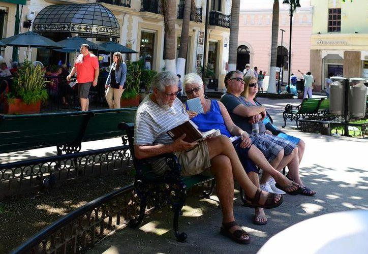 OMT pronostica crecimiento de turismo del 4.5 % a nivel nacional. En la imagen un grupo de turistas en un parque del centro de Mérida. (Milenio Novedades)