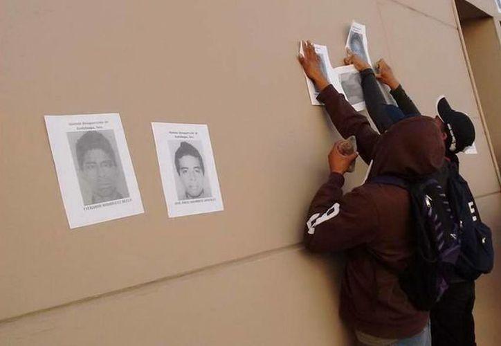 Los normalistas también pegaron en las paredes del edificio de la Fiscalía de Guerrero imágenes de sus compañeros desaparecidos.(twitter/@SubVersionesAAC)