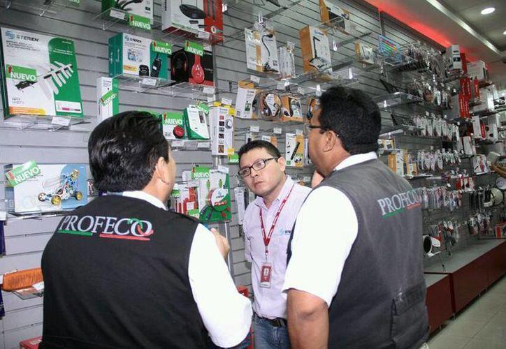 La Profeco anunció que redoblará la vigilancia en los centros de abastos, comercios, súper y mercados para evitar abusos contra los consumidores. Imagen de contexto de dos funcionarios durante la revisión de un comercio. (Archivo/SIPSE)
