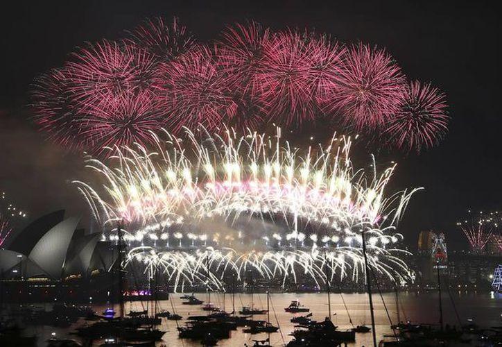 Fuegos artificiales explotan sobre el Opera House y Harbour Bridge durante la víspera de fuegos artificiales de Año Nuevo en Sydney, Australia. (Foto AP / Rob Griffith)