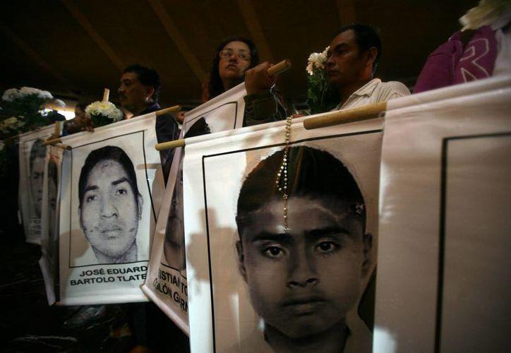 Los padres de los normalistas desaparecidos denuncian que la Procuraduría de Guerrero trató indebidamente los restos hallados en fosas de Iguala. (AP)