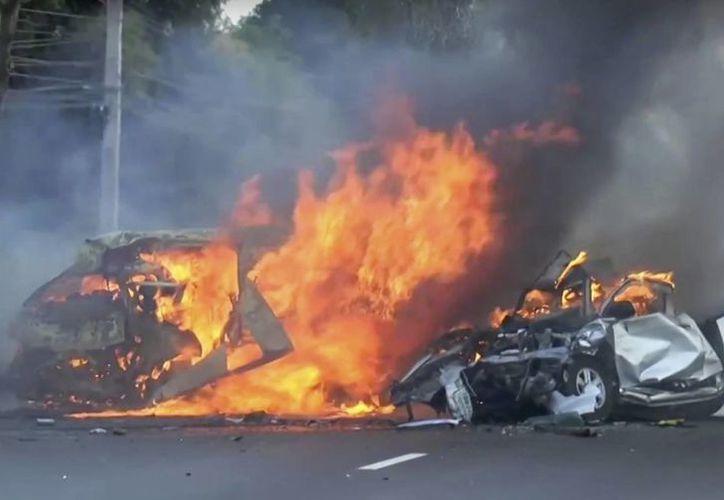 Dos vehículos arden tras colisionar en una carretera en el este de Bagkok, Tailandia, el lunes 2 de enero de 2017. Veinticinco personas murieron y dos resultaron heridas, según las autoridades. (Foto: Matichon TV vía AP)