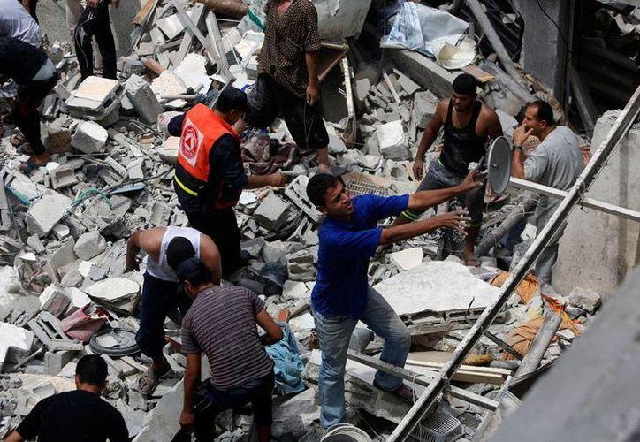Israel lanzó ayer 2 misiles en una casa de la playa, donde falleció una persona y 20 más están desaparecidas. En la imagen, palestinos buscan sobrevivientes debajo de los escombros, horas después del ataque del Ejército hebreo. (AP)