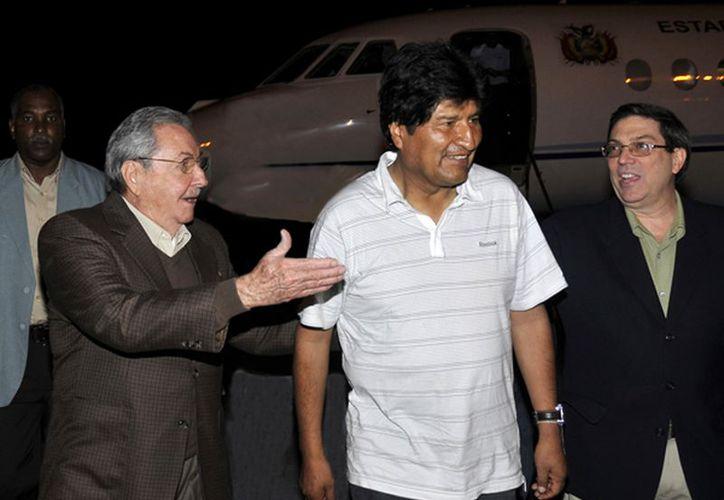 El presidente de Bolivia, Evo Morales (c) es recibido por el presidente Raúl Castro, de Cuba (i) y el Ministro de Relaciones Exteriores de Cuba, Bruno Rodríguez. (Agencias)