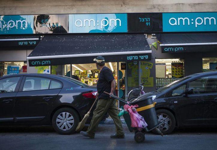 Un barrendero israelí pasa un supermercado abierto las 24 horas en Tel Aviv, Israel. (Agencias)