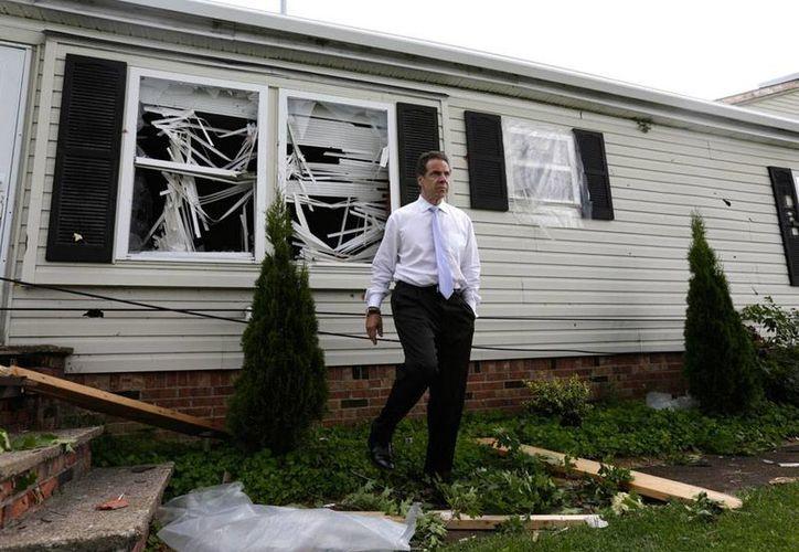 El gobernador de Nueva York, Andrew Cuomo, camina afuera de una vivienda dañada, en Smithfield, donde las tormentas dejaron saldo rojo. (Agencias)