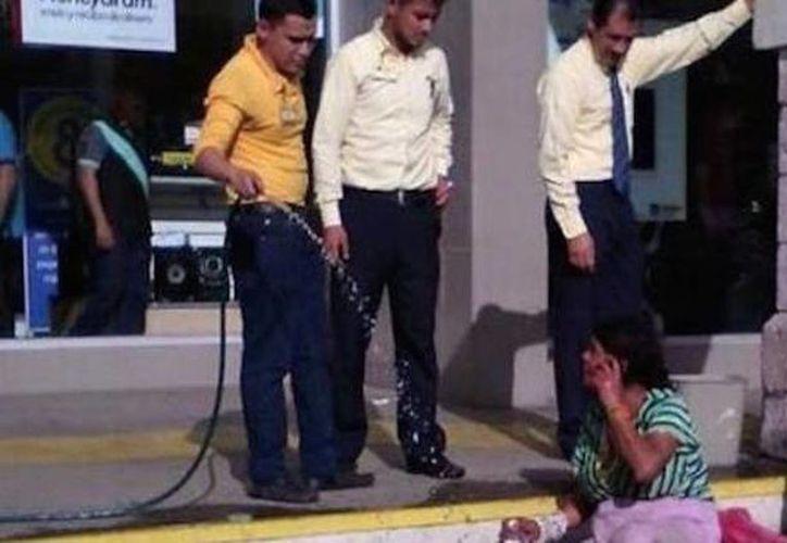 Foto del momento en que los empleados de Coppel Nayarit  insultaron y arrojaron agua a los indigentes para alejarlos del establecimiento. (Imagen tomada de Facebook)