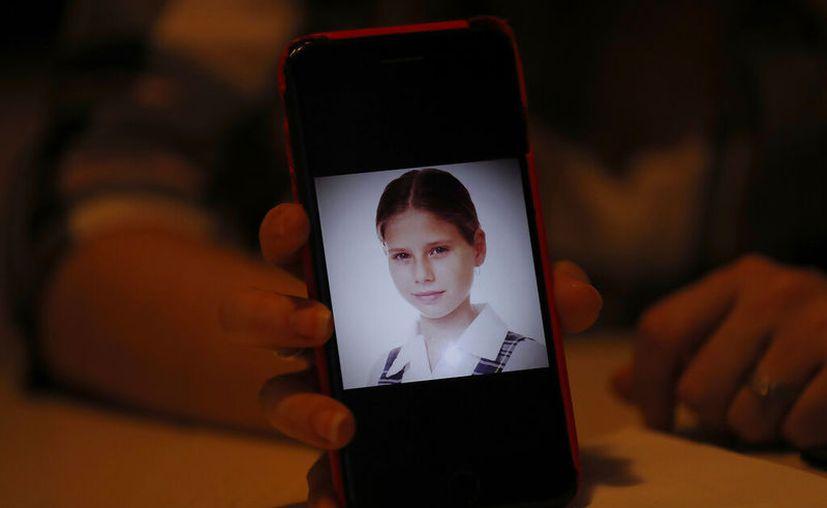 Ana Lucía Salazar muestra una foto suya de cuando tenía ocho años en su celular. (AP Foto/Marco Ugarte)