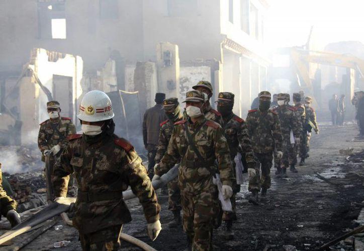 Un incendio en una fábrica de zapatos causó la muerte de 16 personas, y heridas a otras 20, en China, un país donde estos accidente son comunes. En la foto, bomberos entran a la zona siniestrada de La Ciudad de la Luna, donde el sábado pasado el fuego arrasó con 300 construcciones de la ciudad tibetana. (Archivo/Agencias)