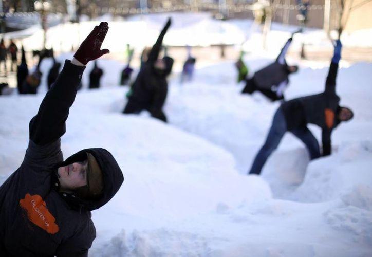 Las nevadas de las últimas semanas han propiciado que muchos estadounidenses tengan que realizar actividades entre nieve. En la imagen, clase de yoga en Minneapolis, Minnesota. (Agencias)