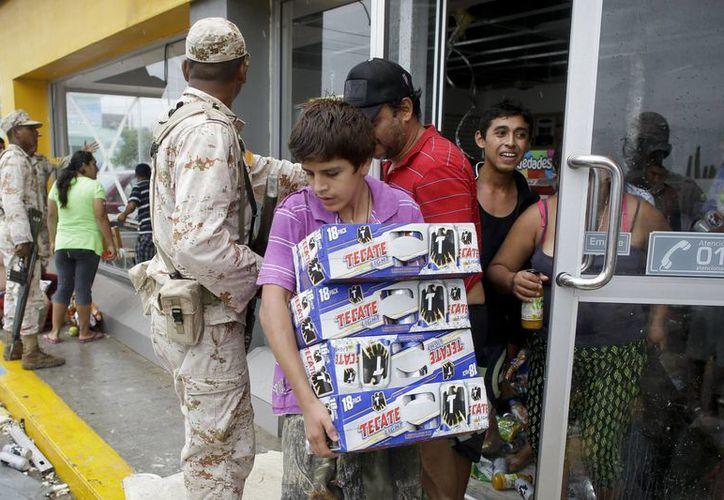 Un menor se aleja con cajas de cerveza de una tienda de conveniencia destruida por el huracán Odile, mientras soldados mexicanos tratan de impedir que la gente siga saqueando la tienda en Los Cabos, BCS. (Agencias)